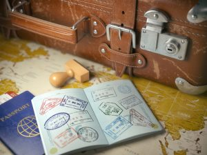 travel visas in passport with suitcase packed
