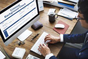 man at computer doing criminal records check