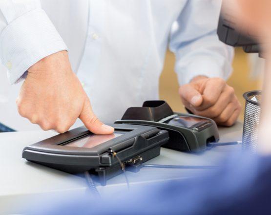 man pressing thumb on fingerprint scanner